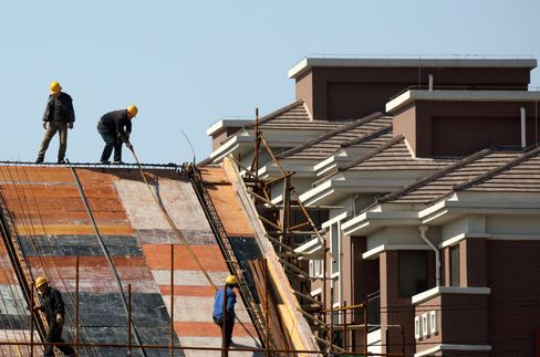 Workers labor on the roof of a house under construction next to residential apartments at the Sino-Singapore Tianjin Eco-city in Tianjin. The government has taken multiple steps since it first began to tackle su