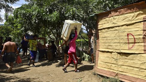 Colombians evicted from homes in Venezuela pass next to a house marked with a