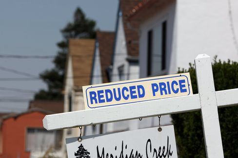 A sign advertising a reduced price is seen in front of a home for sale in Richmond, California. Photographer: Justin Sullivan/Getty Images