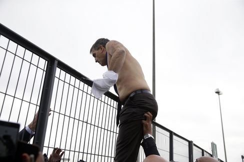 Air France human resources chief Xavier Broseta scales a fence away from protesters in Roissy-en-France, today.