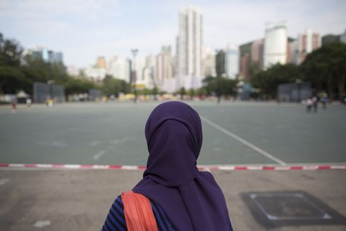 An Indonesian domestic worker looks out towards a football court at Victoria Park in Hong Kong. Photographer: Jerome Favre/Bloomberg