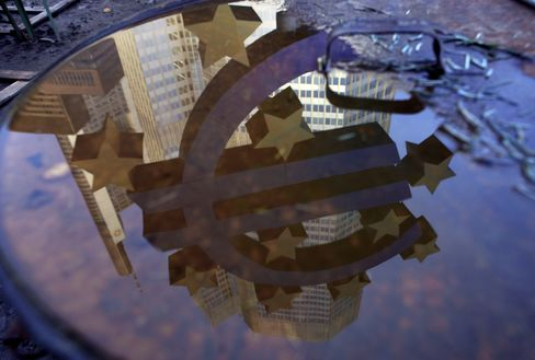 A Euro sign sculpture is reflected in a pool of water outside the European Central Bank's headquarters in Frankfurt. Photographer: Hannelore Foerster/Bloomberg