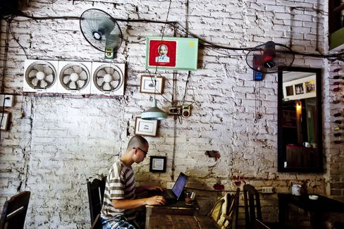 A customer uses a computer at a cafe in Hanoi. As Asians switch from traditional occupations, farms and factories, the contribution of service industries to the region's economy is poised to exceed 50 percent for the first time, according to data compiled by Bloomberg from government statistics. Photographer: Justin Mott/Bloomberg