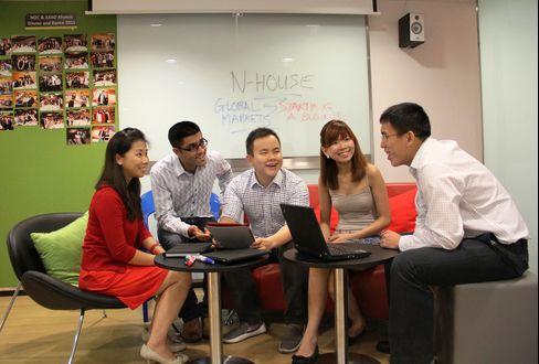 Aspiring entrepreneurs from NUS Enterprise discuss ideas with an alum, right, from the NUS Overseas Colleges program and iLEAD program in the common room at N-House, Singapore. Source: NUS Enterprise via Bloomberg