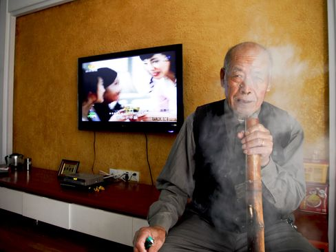 76-year-old Yang Caiguan smokes a bamboo water pipe at his apartment in the Songlinyuan development. Photographer: Qilai Shen/Bloomberg