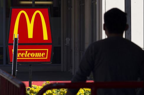 A Pedestrian Walks Past McDonald's Corp. Signage
