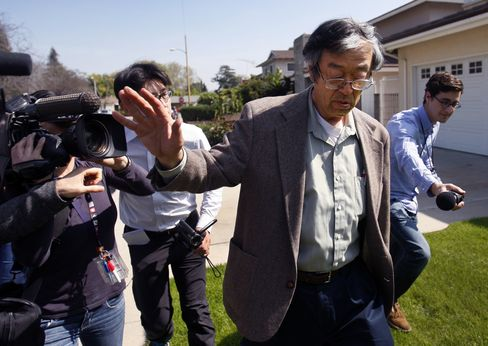 A man named Satoshi Nakamoto, one of many people believed to be the creator of bitcoin, fends off photographers. He's denied involvement.