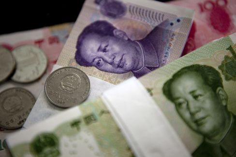 Chinese yuan banknotes and coins are arranged for a photograph in Beijing, China. Photographer: Nelson Ching/Bloomberg