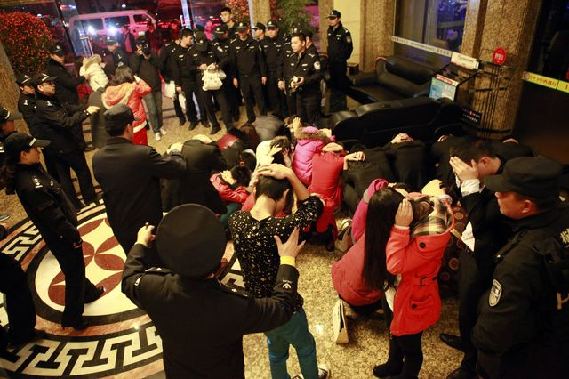 Police arrest alleged sex workers and clients at an entertainment center in Dongguan on Feb. 9, 2014. Source: AFP/Getty Images