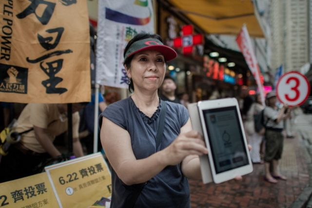 A pro-democracy activist holds a tablet showing an app to vote online outside a polling station in Hong Kong.