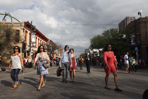 Pedestrians walk around Sixth street in Austin, Texas.