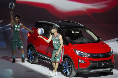 Performers take part in a event to introduce the Yuan, the latest Plug-in Hybrid mini SUV from BYD.