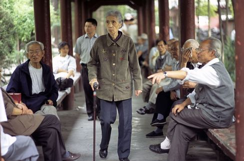 Group of people chatting and walking under a covered walkway at a Buddhist temple compound - Wenshu Temple - Chengdu - Sichuan Province, China