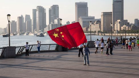 A man launches a kite in the shape of the Chinese national flag on the Bund in Shanghai. China's policymakers are seeking ways to clean up mounting bad loans at the nation's banks, which are at their highest levels in a decade amid slowing economic growth and government moves to curb overcapacity in manufacturing.