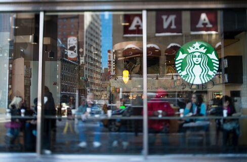 Customers Sit inside a Starbucks Coffee Shop in New York