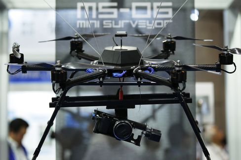 A Sony digital camera is attached to the Autonomous Control Systems Laboratory Ltd. Mini Surveyor MS-06LA multi-rotor unmanned aerial vehicle (UAV), manufactured by Kikuchi Seisakusho Co.