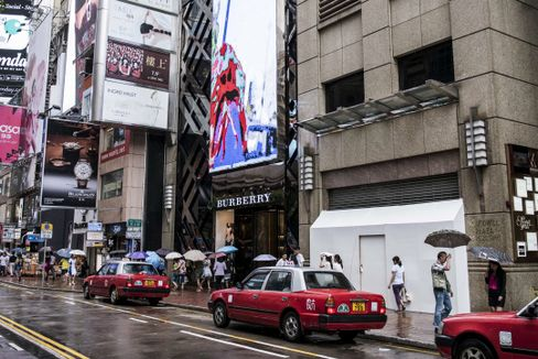 Shoppers and pedestrians walk past a Burberry Group Plc store, center, and a shuttered store vacated by Tag Heuer International SA on Russell Street in Hong Kong. Photographer: Xaume Olleros/Bloomberg