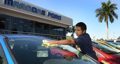 An auto detailer cleans the windshield of a 2012 Ford Motor Co. Focus vehicle at a Maroone car dealership in Ft. Lauderdale, Florida. Photographer: Mark Elias/Bloomberg