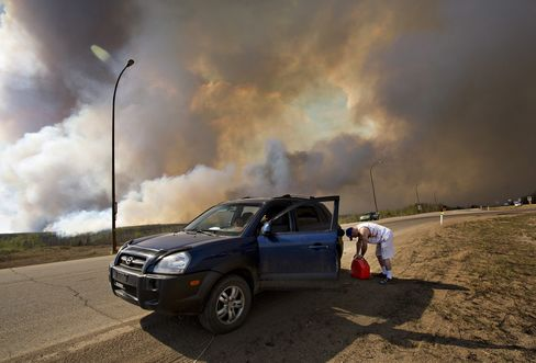 An evacuee puts gas in his car on his way out of Fort McMurray, on May 4.