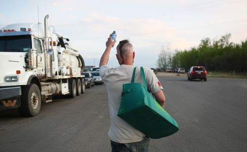 A man hands out bottles of water to people fleeing their homes.