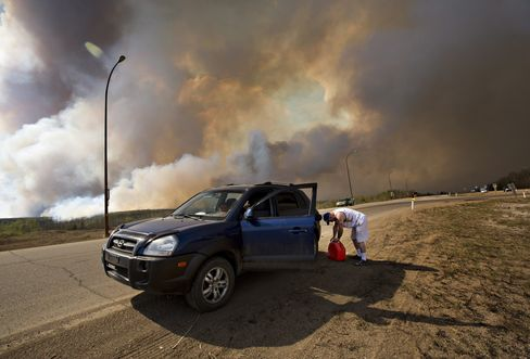 An evacuee puts gas in his car on his way out of Fort McMurray on May 4.