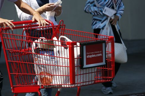 A Shopper Pushes a Cart Outside a Staples Store