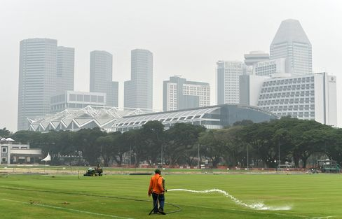 A worker waters a field as buildings are shrouded in haze in Singapore on Oct. 5.