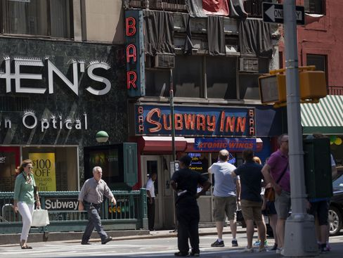 Pedestrians pass the Subway Inn bar in New York on July 25, 2014.  Photographer: Michael Nagle/Bloomberg