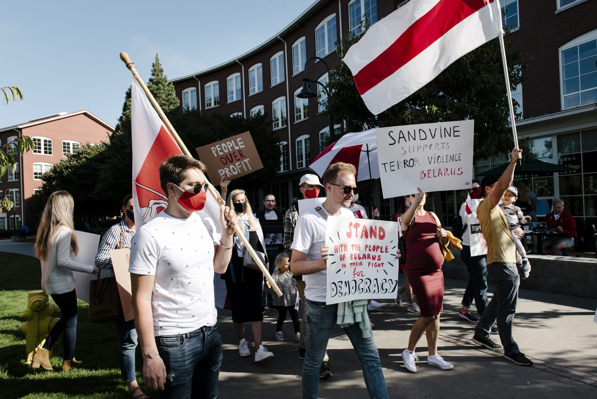 Demonstrators hold signs and wave Belarus flags during a protest outside Francisco Partners headquarters in San Francisco, California, onSept. 18.