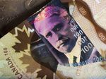 Canadian one hundred dollar banknotes depicting Former Prime Minister Sir Robert Borden and a Canadian one dollar coin