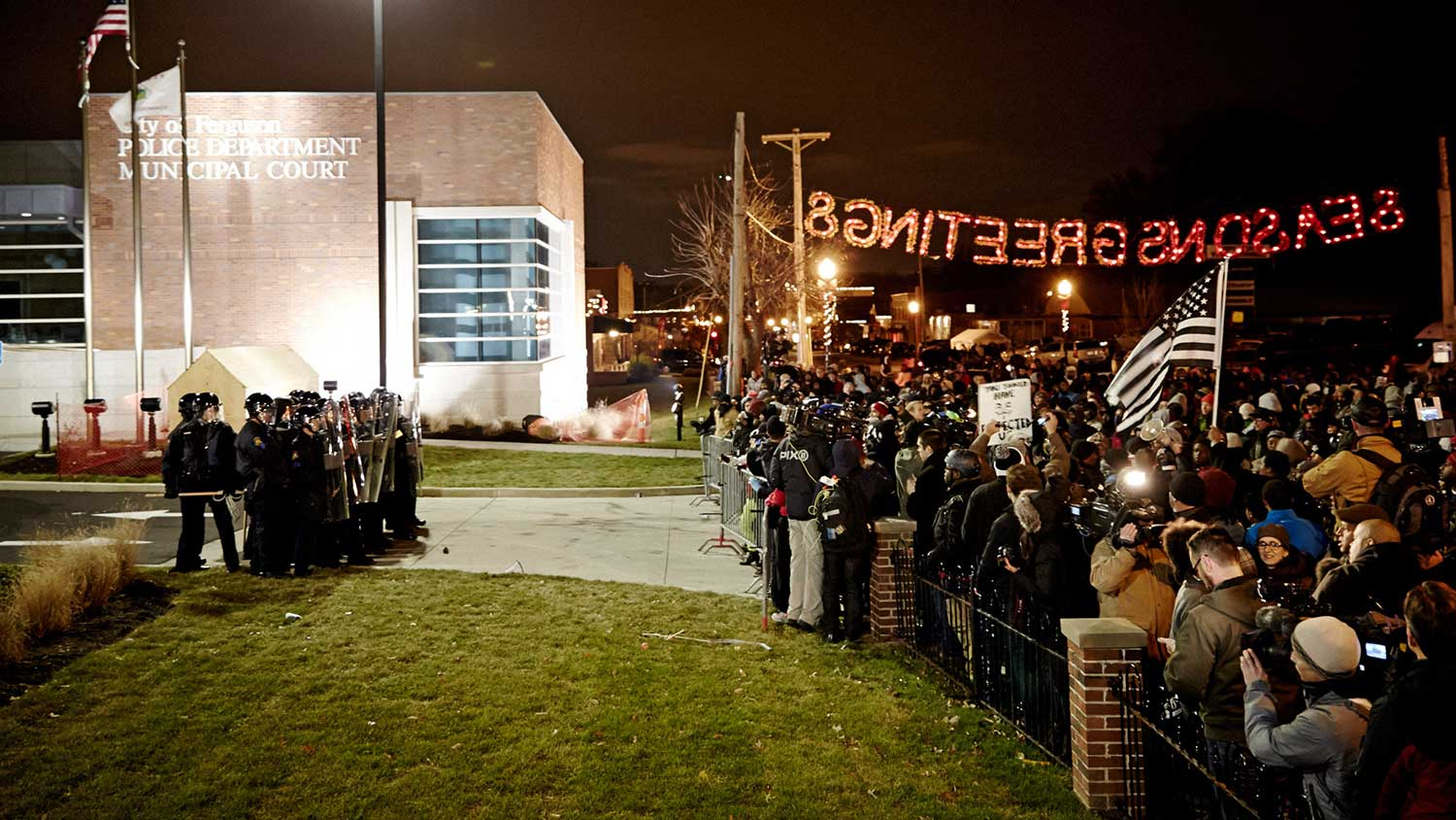 "Protesters wait in front of the Ferguson Police Department beneath a ""Seasons Greetings"" sign."