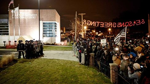 """Protesters wait in front of the Ferguson Police Deparment beneath a """"Seasons Greetings"""" sign."""
