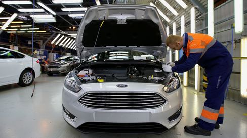 An employee performs a quality control inspection of a new Ford Focus