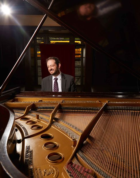 Adrian Banner tries out the piano at the Carlton Hotel in New York.