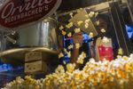 A worker scoops popcorn at a concession stand inside a Cinemark Holdings Inc. movie theater.