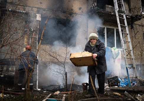 A resident tries to salvage her belongings from a heavily damaged building after shells were exchanged between pro-Russian rebels and Ukrainian forces in Donetsk on Feb. 9, 2015.