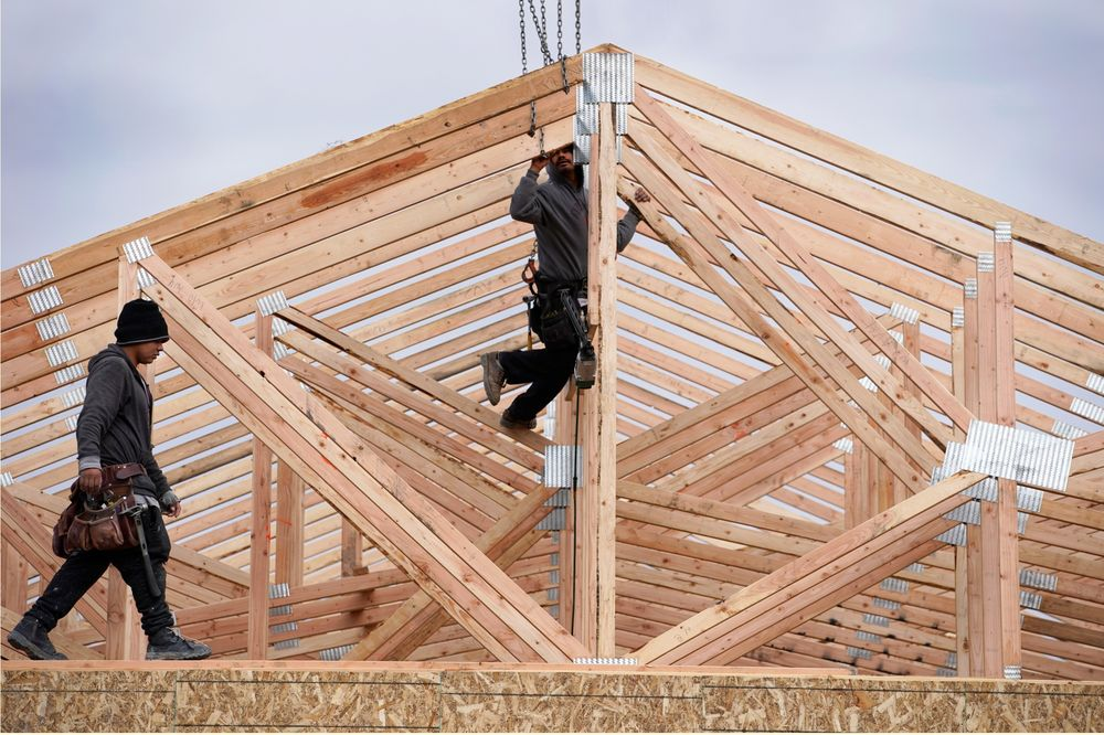 Workers install roof trusses on a home under construction in Vineyard, Utah.