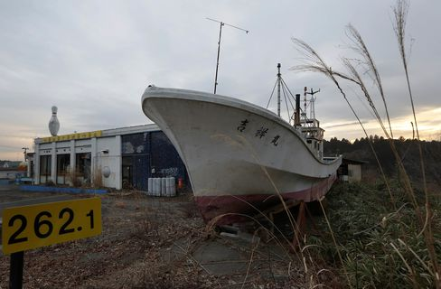 A fishing boat swept inland by a tsunami following the 2011 earthquake sits next to a bowling alley in an evacuation zone in Namie, Fukushima.