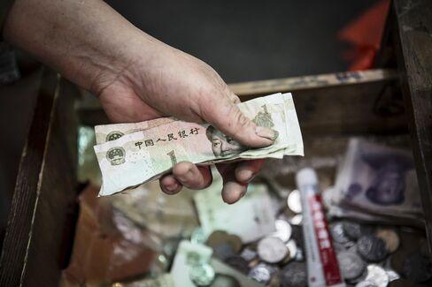 上海の店先で数えられる人民元紙幣
