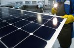 An employee of SunPower Corp. trims the edges and checks solar panels at the SunPower Corp.