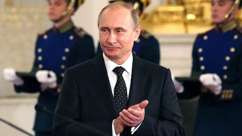 Russian President, Vladimir Putin applauds during a presentation ceremony of state awards marking the Day of Russia in the Grand Kremlin Palace in Moscow on June 12, 2015.