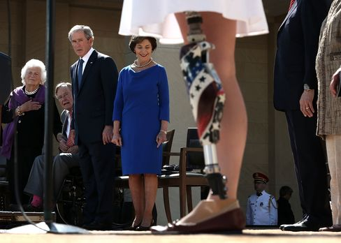 U.S. Army 1st Lt. Melissa Stockwell (Ret.), the first female American soldier to lose a limb in the war in Iraq, recites the Pledge of Allegiance as former President George W. Bush looks on during the opening ceremony of the George W. Bush Presidential Center on April 25, 2013.