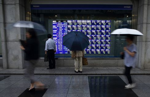 Pedestrians holding umbrellas walk past an electronic stock board outside a securities firm in Tokyo, Japan, on Wednesday, July 8, 2015. Japanese stocks fell, with the Topix index dropping by the most in more than a year, amid concern that ChinaÕs equity rout is spreading.