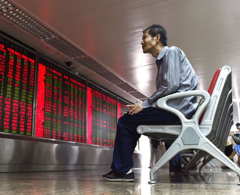 An investor looks at a board showing stock market movements at a securities company in Beijing on July 10, 2015.
