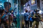 People look at riot police stop and search people outside a shopping mall at Mong Kok in Hong Kong, China, on Monday, Aug. 31, 2020.
