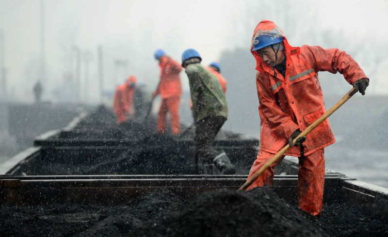 Workers work on the coal carriages at a railway station in China's Jiangxi province.
