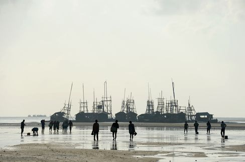 Workers walk to work to wooden dredging platforms on a beach on Bangka Island, Indonesia. Photographer: Dimas Ardian/Bloomberg