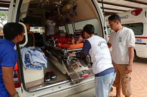 Paramedics tend to a collapsed girl as she is loaded onto one of Bantaeng's ambulances, which promise to reach patients within 20 minutes.
