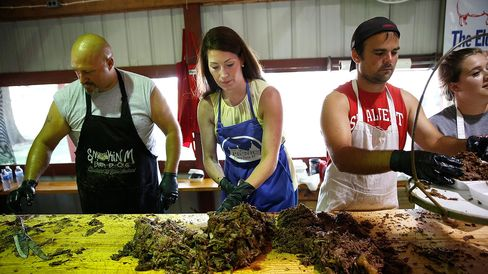 Democratic Senate nominee Alison Lundergan Grimes chops mutton barbeque at the Elder Family's barbeque stand at the Fancy Farm picnic Aug. 2, 2014, in Fancy Farm, Ky.