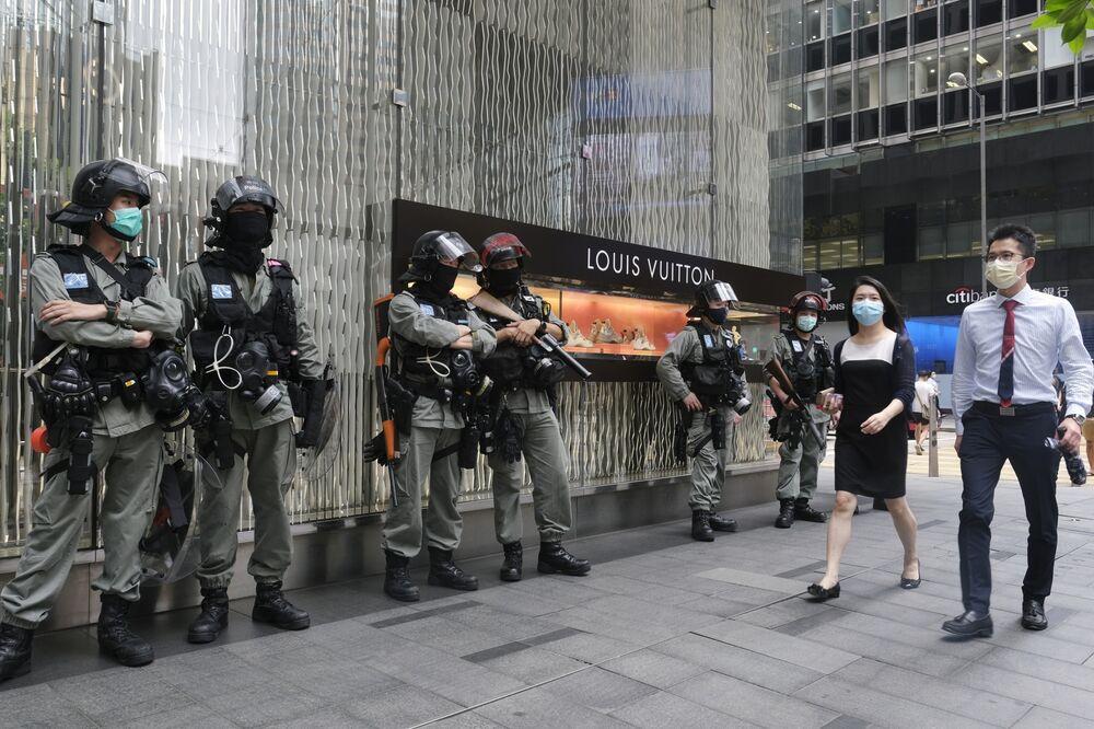 Cảnh sát chống bạo động đứng trước một cửa hàng bán đồ xa xỉ Louis Vuitton ở quận trung tâm ở Hồng Kông, Trung Quốc, vào ngày 28 tháng 5. Nhiếp ảnh gia: Roy Liu / Bloomberg